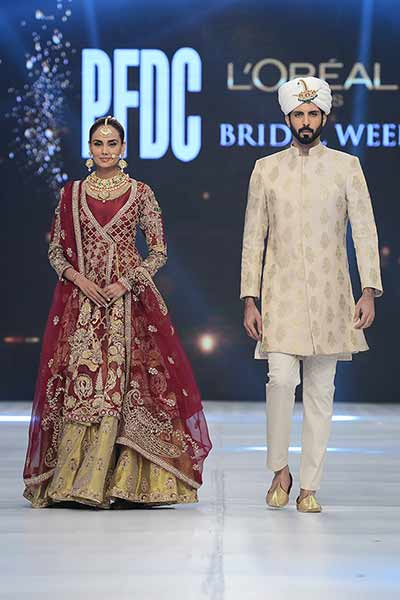 Bridal in traditional red and golden short shirt with golden lehnga and red dupatta and groom in cream sherwani with turban and trouser latest indian and pakistani wedding matching dress combinations for bride and groom 2017