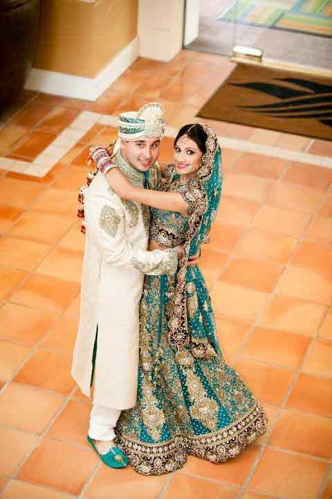 Bride in zink green lehnga choli with dupatta and groom in white sherwani with matching zink green turban latest indian and pakistani wedding matching dress combinations for bride and groom 2017